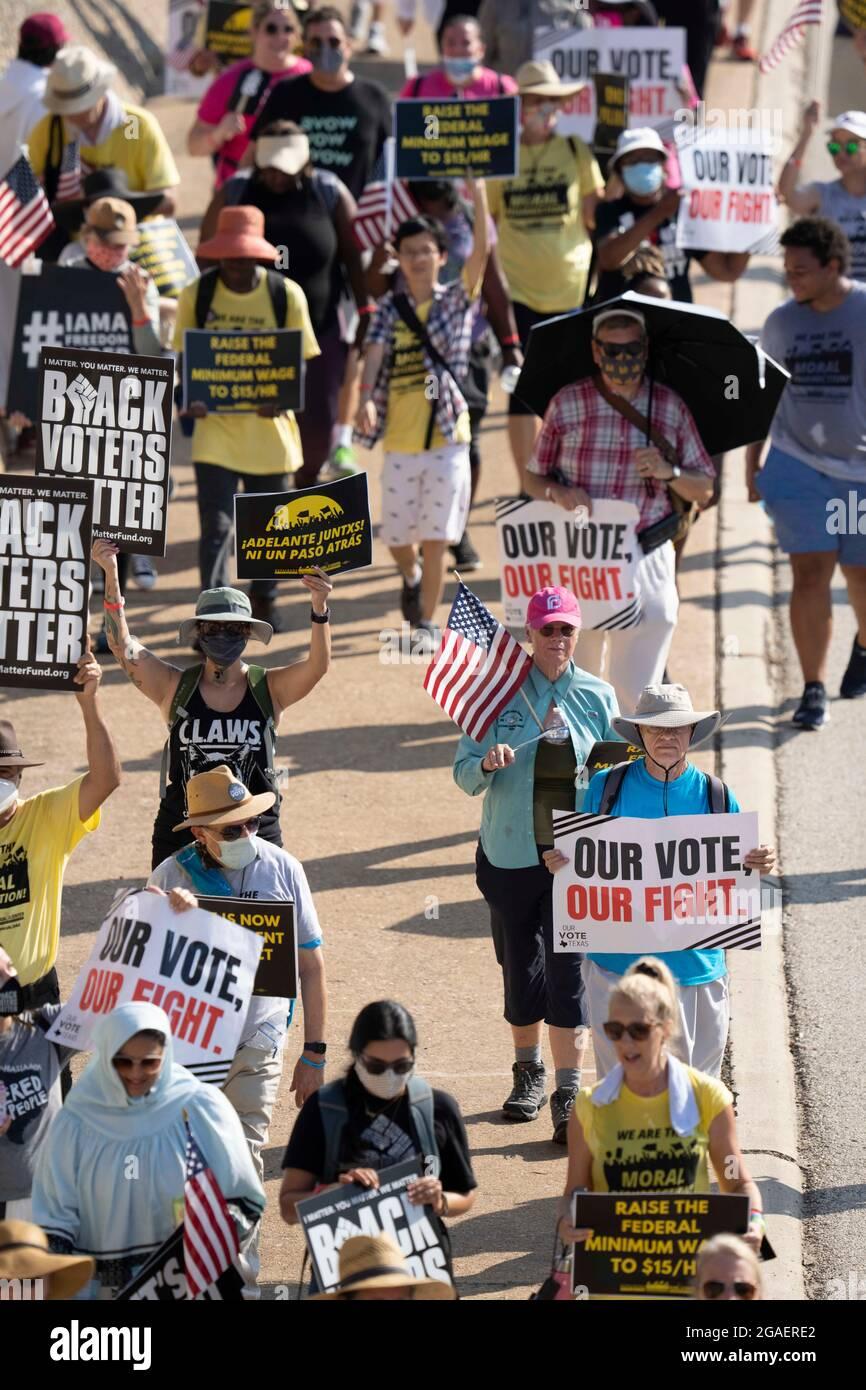 Austin, Texas, États-Unis, 30 juillet 2021 : les groupes de droits de vote défilent le long d'une route de desserte autoroutière vers le capitole du Texas depuis le nord d'Austin le troisième jour d'un voyage de 30 miles protestant contre les efforts des Républicains pour supprimer les votes dans tout le pays et au Texas. Des changements de marcheurs se font échanger dans un effort pour lutter contre la chaleur oppressive du Texas. Crédit : Bob Daemmrich/Alay Live News Banque D'Images