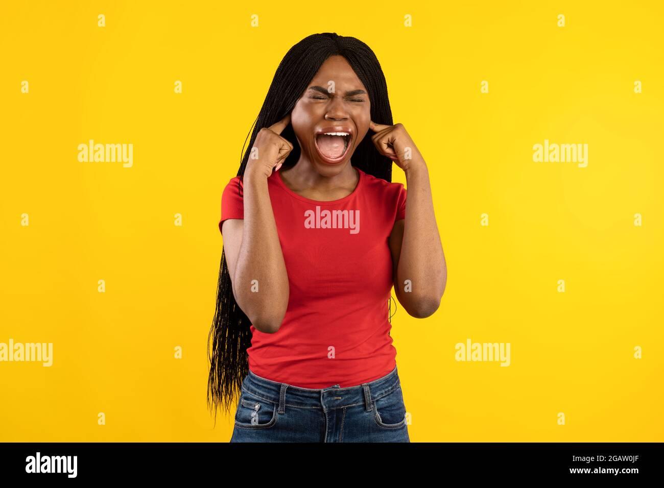 Emotive Black Femme criant couvrant les oreilles avec les doigts se tenant sur fond jaune. Photo de la dame hurlant en studio avec les yeux fermés. Je n'ai pas de Wa Banque D'Images