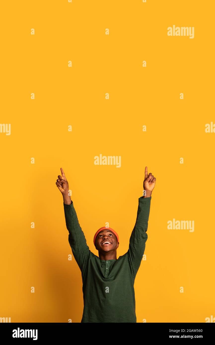 Vérifiez ceci. Joyeux homme afro-américain pointant vers le haut à l'espace de copie au-dessus de sa tête avec deux mains, heureux Noir Hipster homme démontrant la place libre pour Banque D'Images