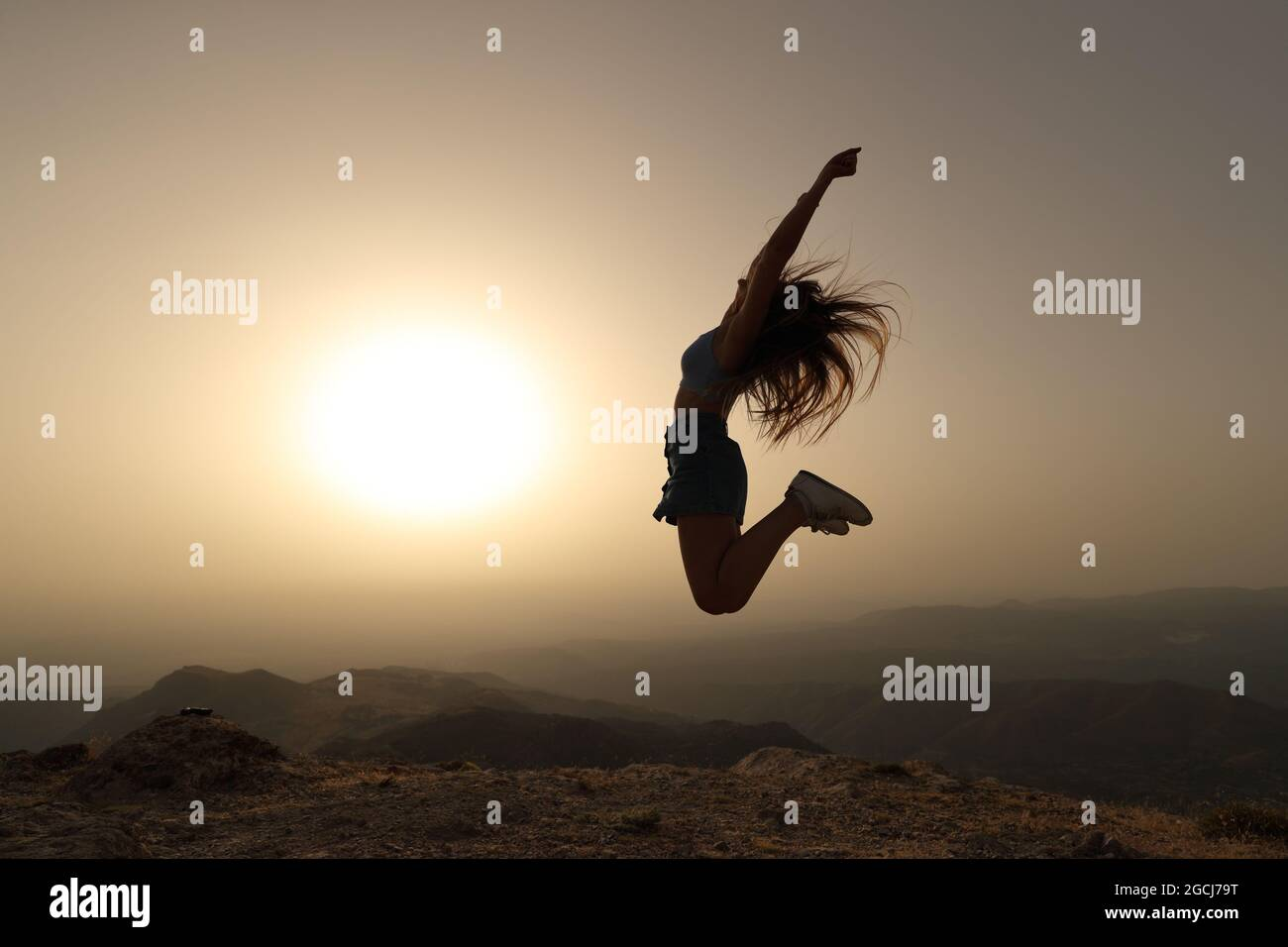 Vue latérale d'une silhouette de femme sautant au coucher du soleil dans la montagne Banque D'Images