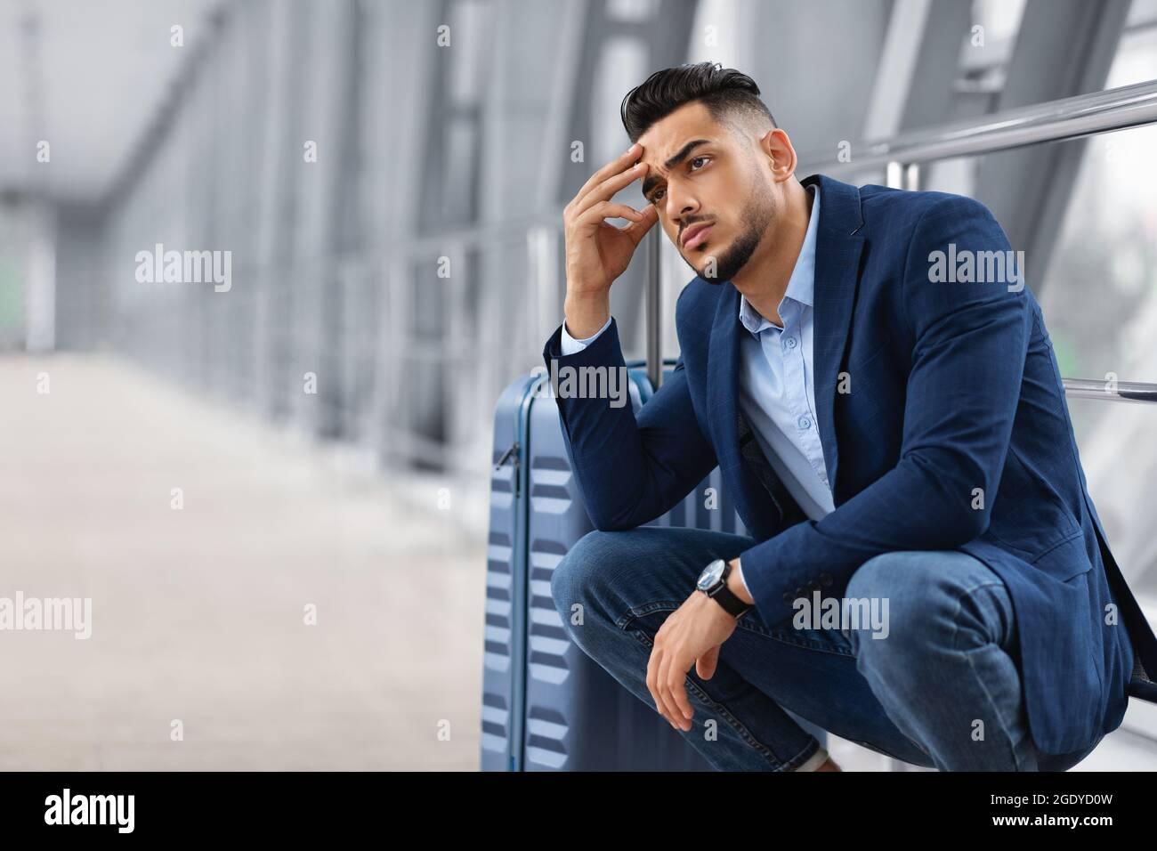 Retard de vol. Un homme arabe pensif attend avec ses bagages dans le terminal de l'aéroport Banque D'Images