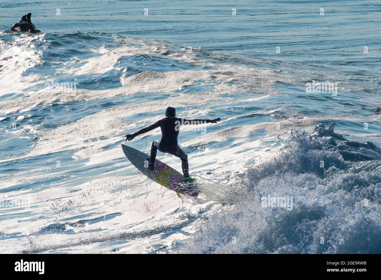 Un surfeur effectuant un tour d'avion à cheval sur une vague dans la baie de Fistral à Newquay, en Cornouailles. Banque D'Images