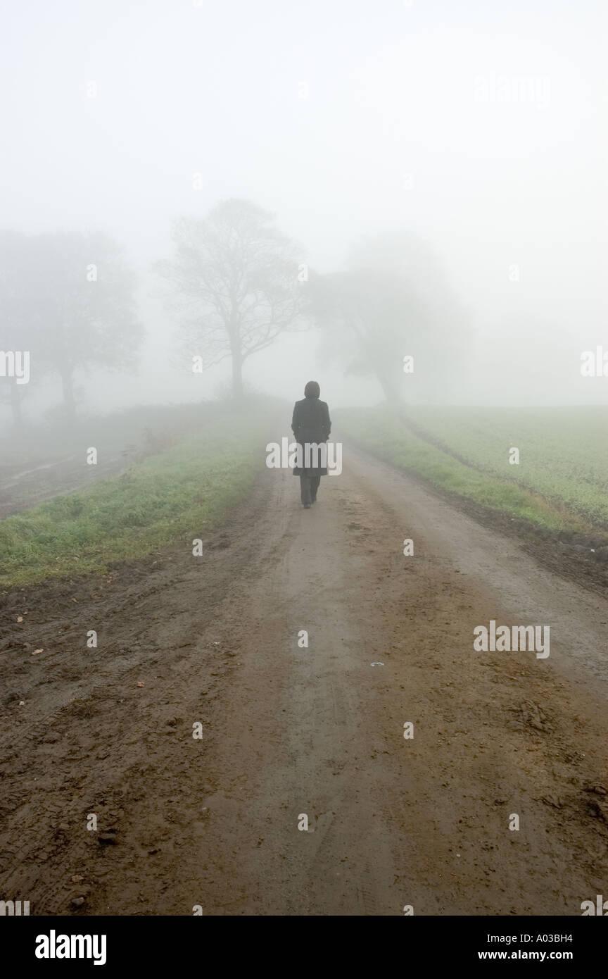 Scène de brouillard atmosphérique d'une femme a perdu le long d'une route de campagne isolée Photo Stock