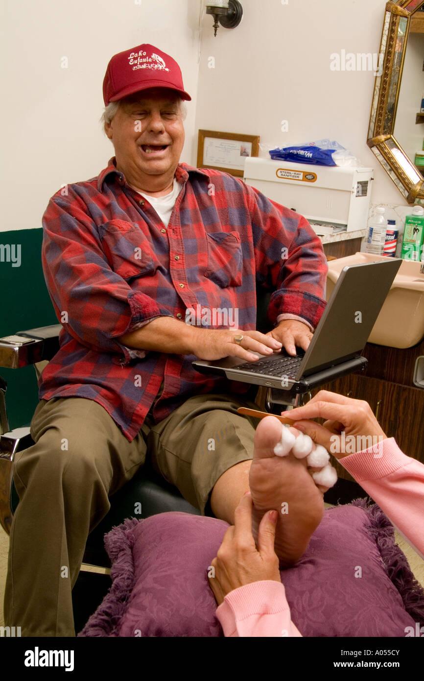 Petit centre ville salon de coiffure pour homme en Amérique type camionneur obtenir une pédicure tout en travaillant sur un ordinateur portable situation étrange humo Photo Stock