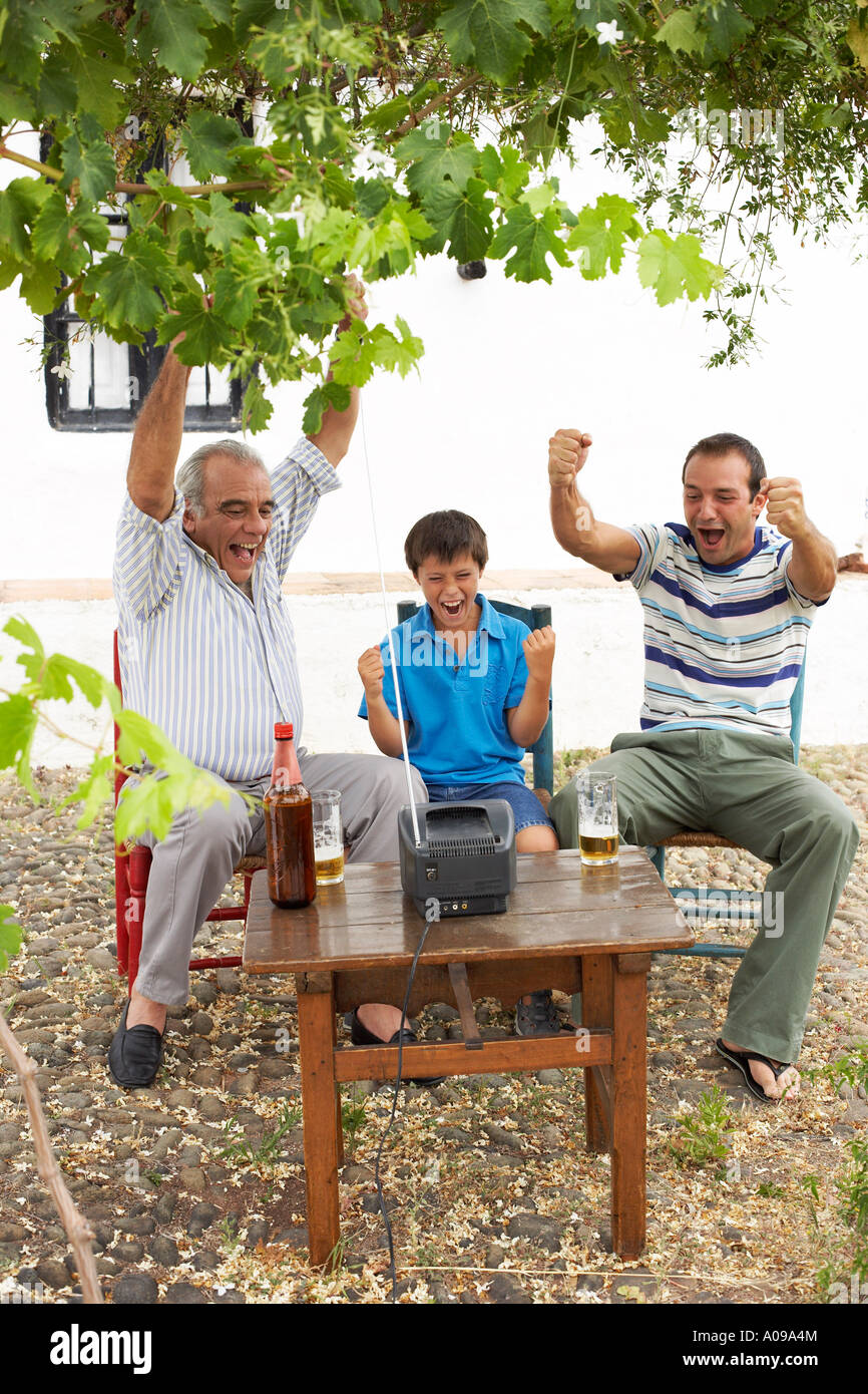 Grand-père, père et fils à regarder la télévision en arrière-cour Banque D'Images