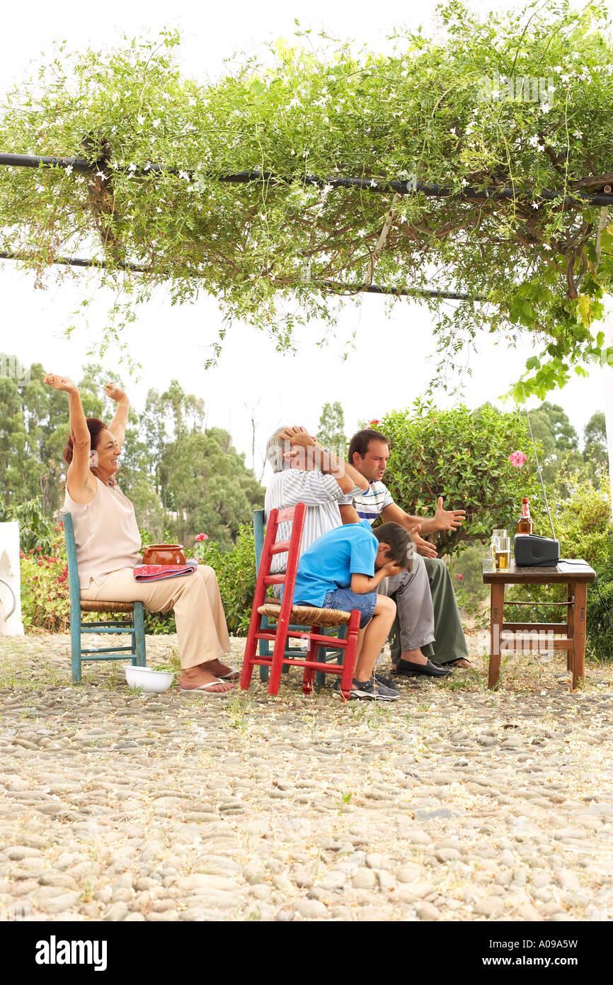Grand-père, la grand-mère, père et fils à regarder la télévision en arrière-cour Banque D'Images