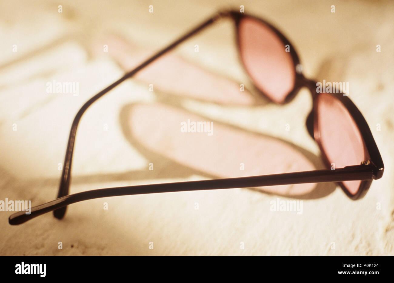Une paire de lunettes teintées de rose jette une ombre sur une surface  blanche texturée Photo bb4c058c2639