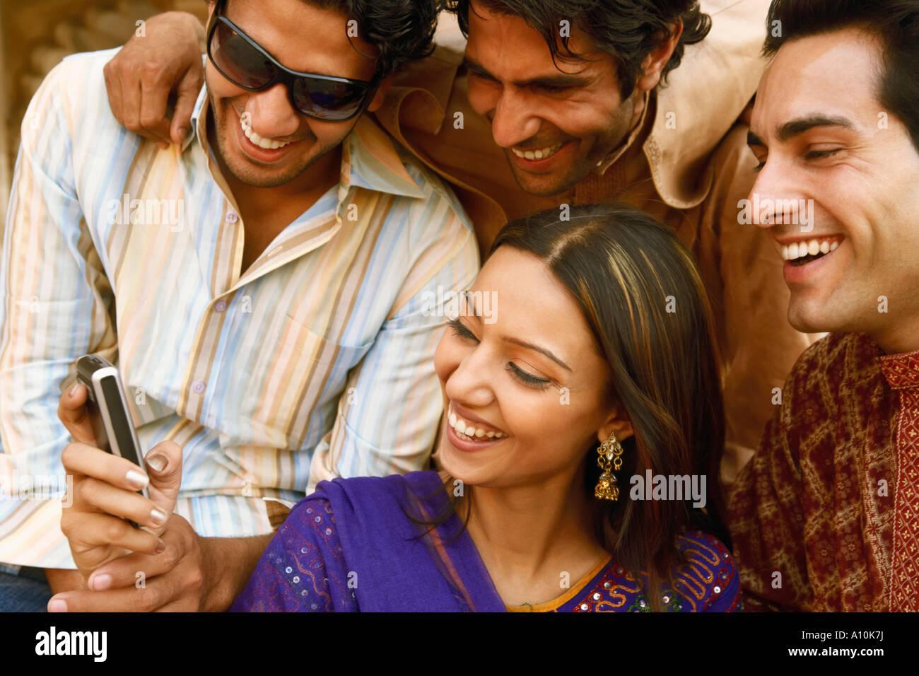 Close-up de trois jeunes hommes et une jeune femme à la recherche d'un téléphone mobile et souriant, Photo Stock