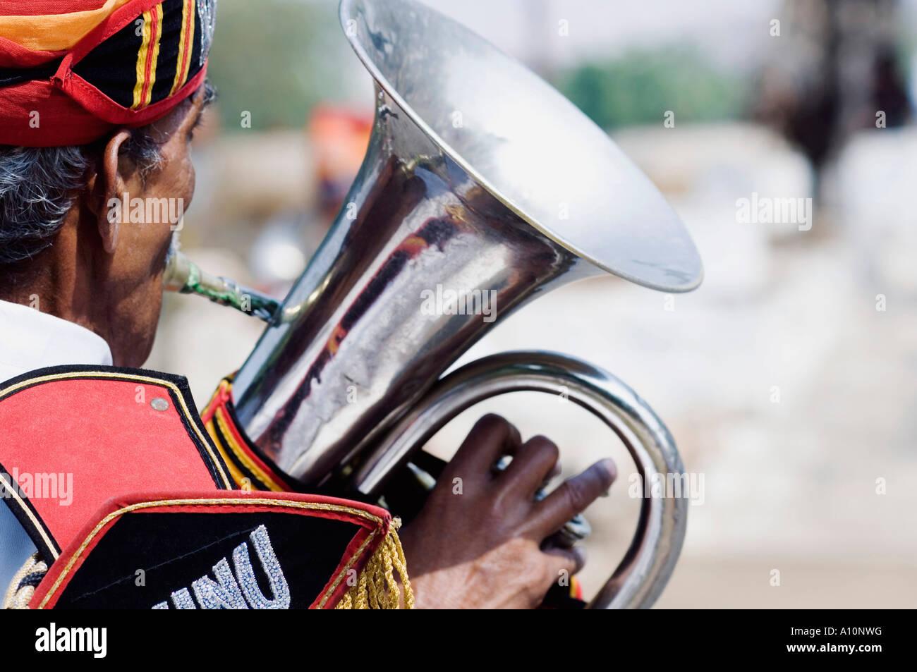Vue arrière d'un homme jouant du tuba, Jaipur, Rajasthan, Inde Photo Stock