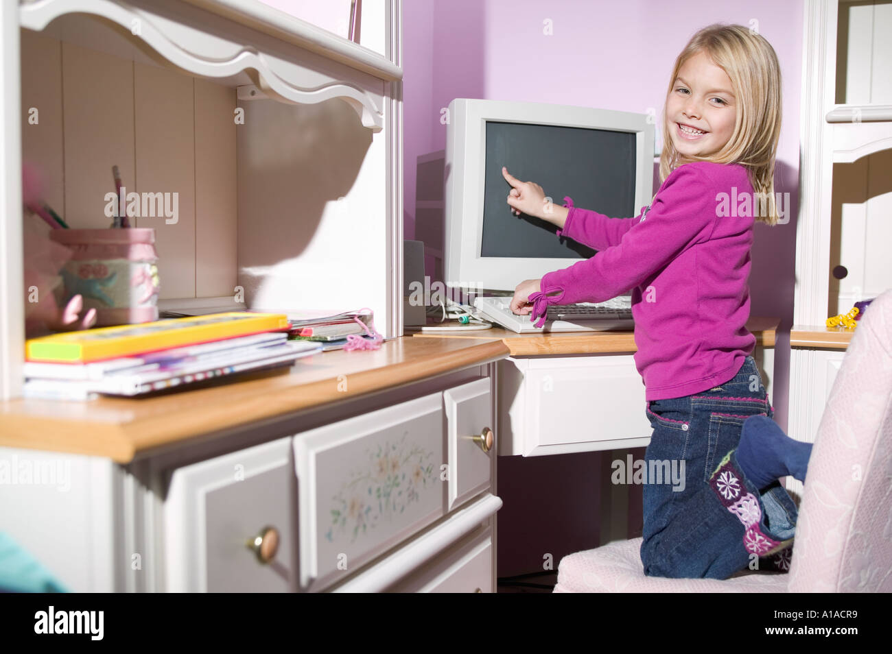 Girl pointing at computer screen Photo Stock