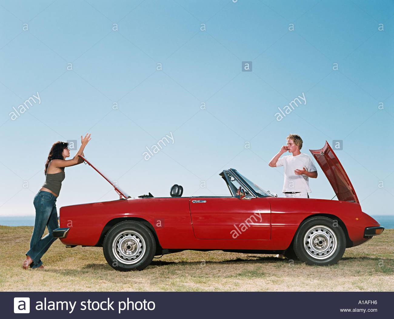 Couple ayant une voiture en panne Photo Stock