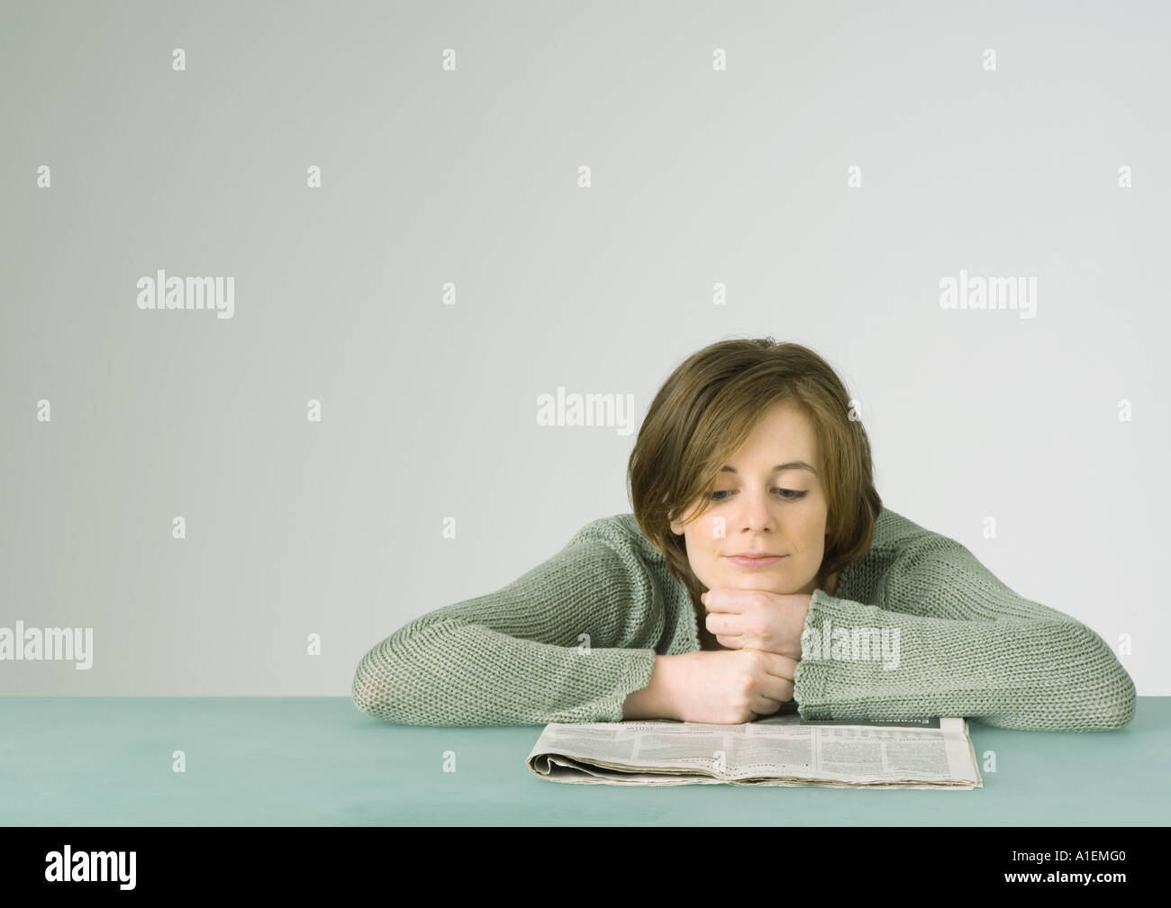 Young woman leaning on table, reading newspaper Photo Stock