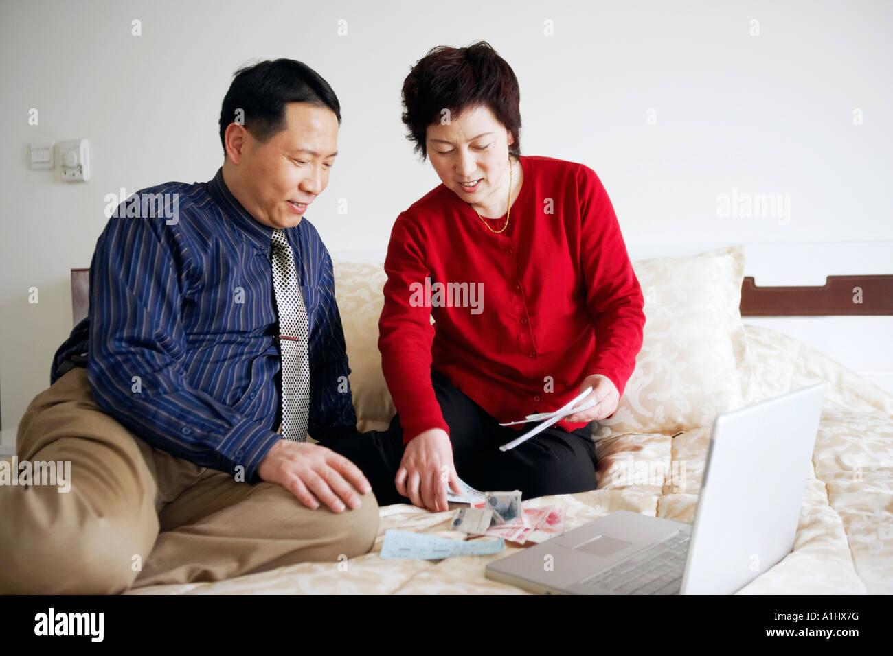 High angle view of a young couple assis sur le lit avec du papier-monnaie et d'un ordinateur portable Banque D'Images