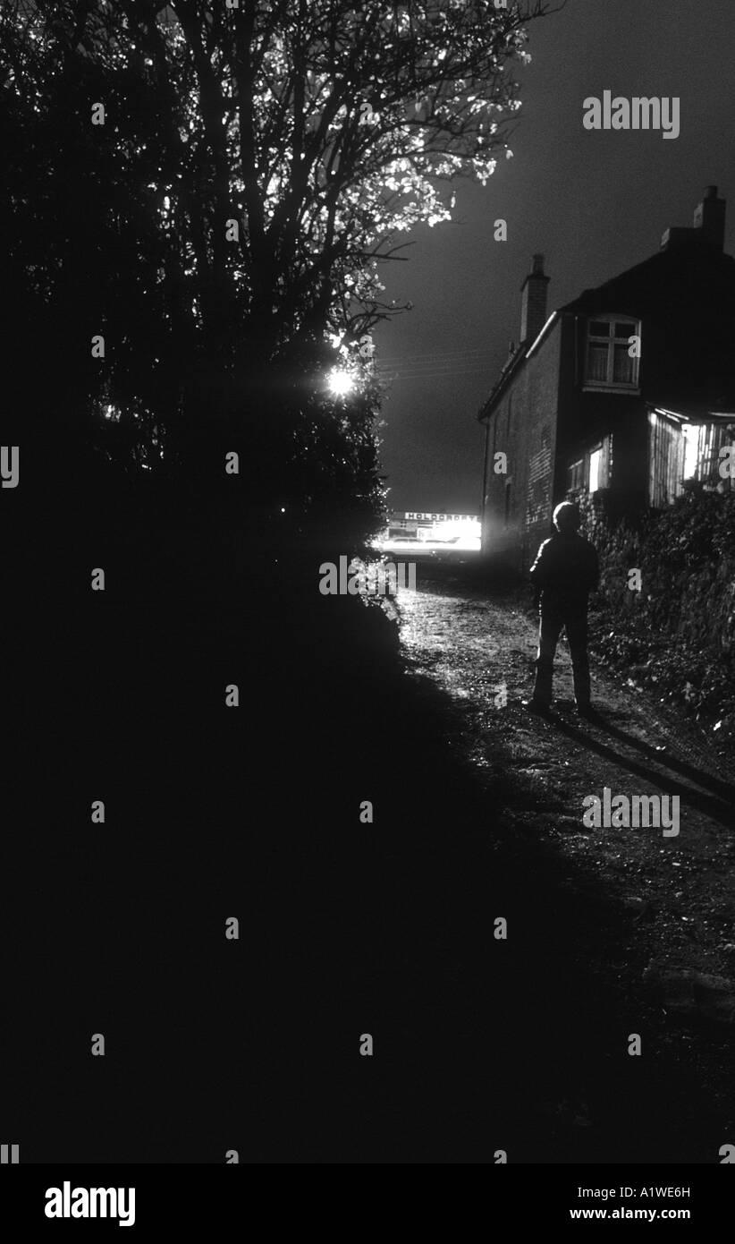 Silhouetté Figure d'un homme debout dans une ruelle la nuit, illuminé par les feux de route. Photo Stock