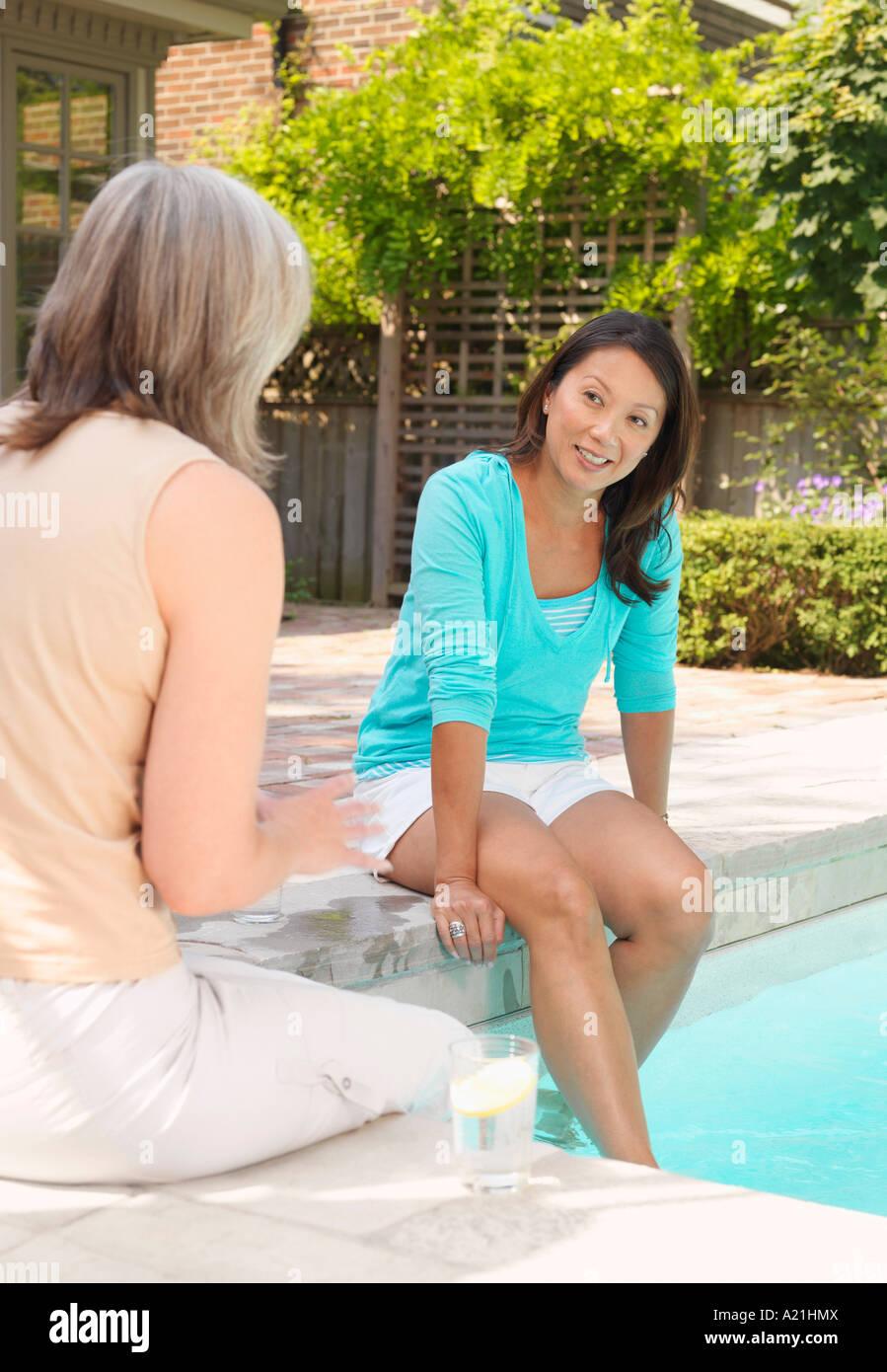 La femme assise à côté de la piscine Banque D'Images