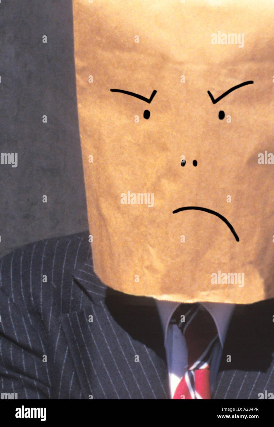 Businessman avec sac en papier brun sur la tête, fronçant Photo Stock