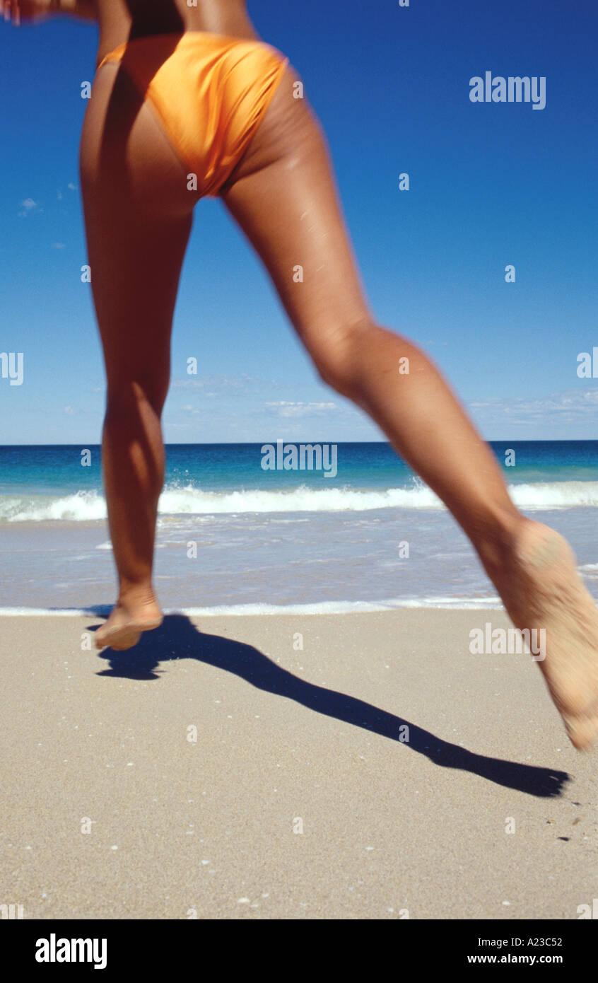 Jeune femme en bikini orange courir vers ocean Photo Stock