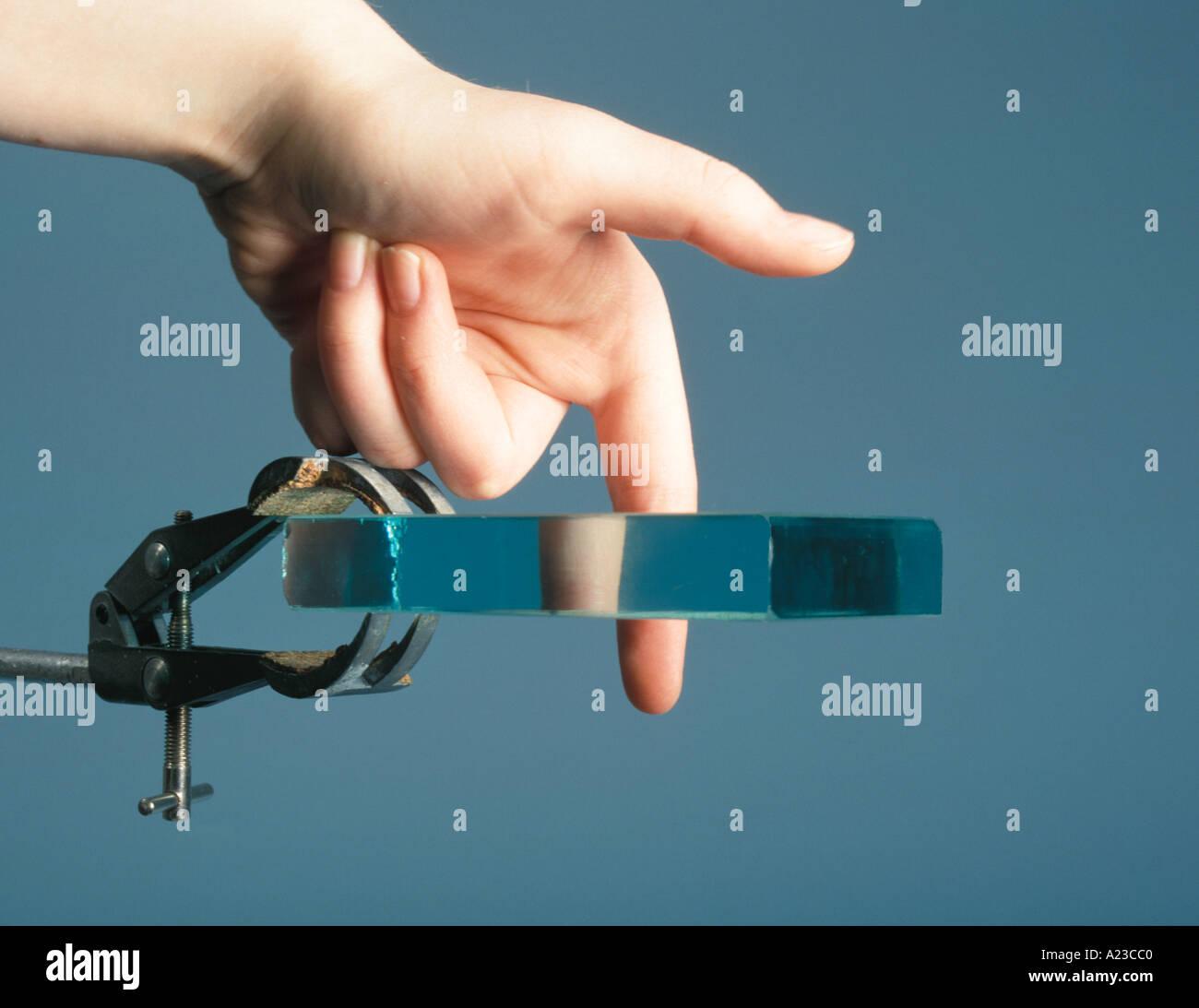 Un doigt semble avoir un morceau manquant lors de la vue à travers un bloc de verre en raison de la réfraction de la lumière Photo Stock