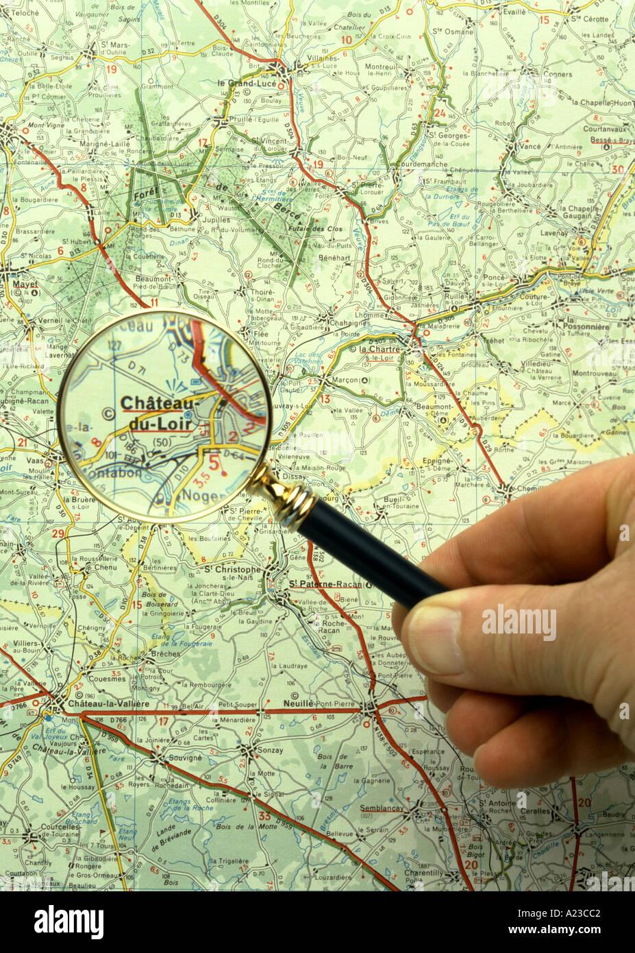 On utilise une loupe pour lire une carte française Photo Stock