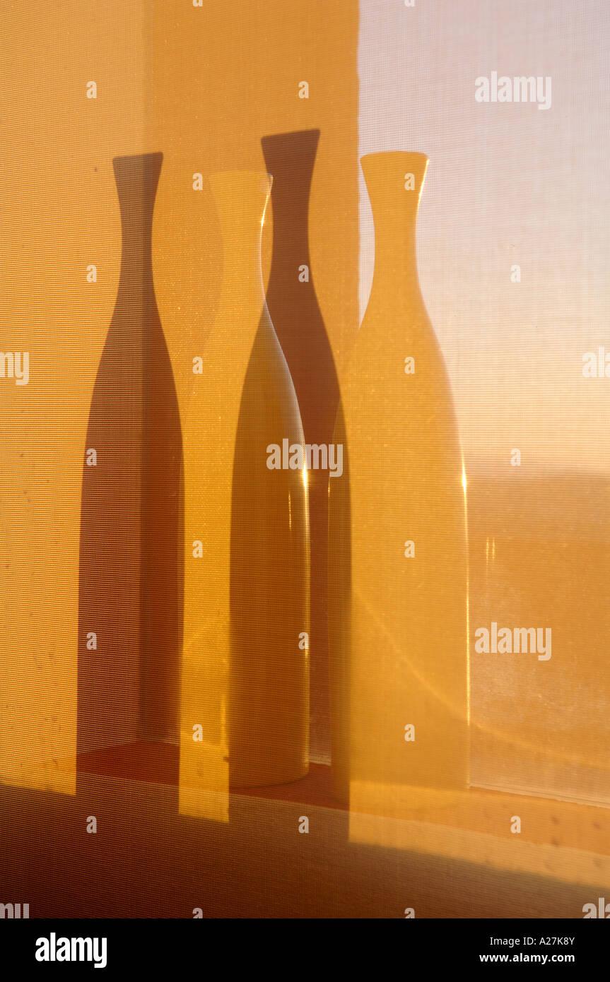 Vases en forme de bouteille dans un jeu de lumière et d'ombre Photo Stock