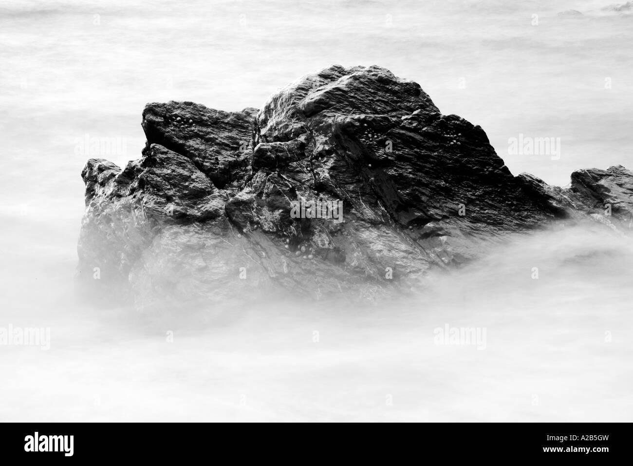 Monochrome noir et blanc d'un rocher baigné par les vagues de la côte de la mer Photo Stock