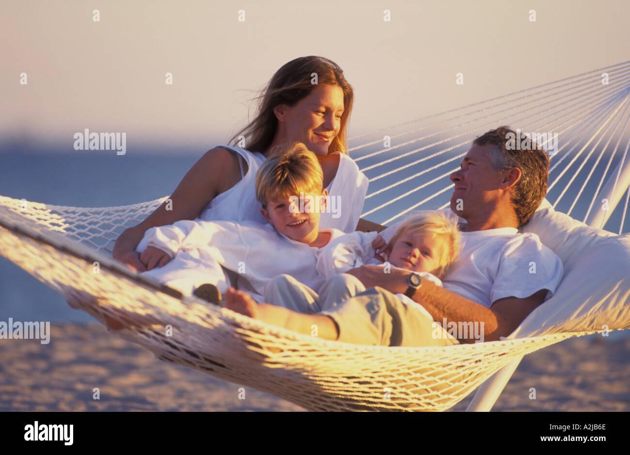 Père et mère de leurs deux enfants couchés ensemble dans un hamac sur la plage Photo Stock