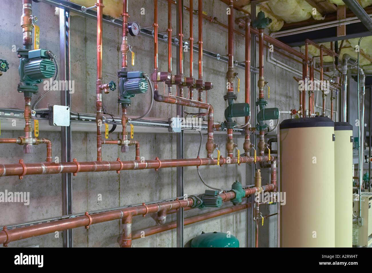 Les tuyaux d'eau en cuivre métal avec chauffe-eau au sous-sol Photo Stock