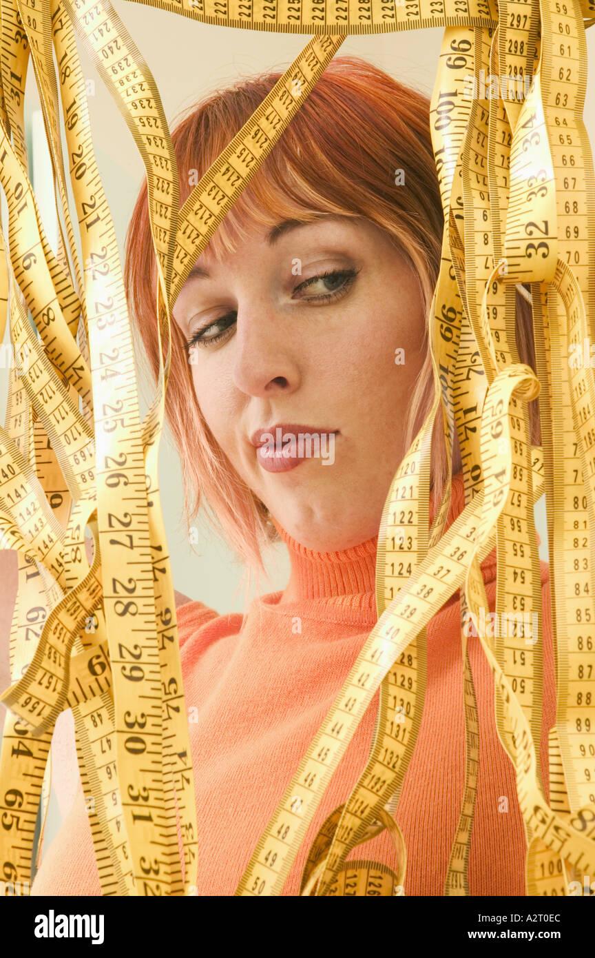 Une jeune femme entourée de rubans à mesurer Photo Stock