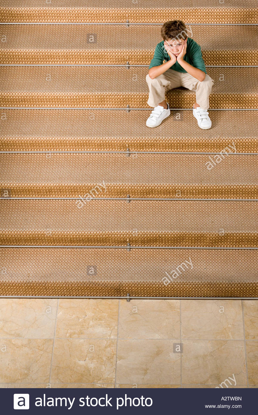 Bored boy sitting on stairs Banque D'Images