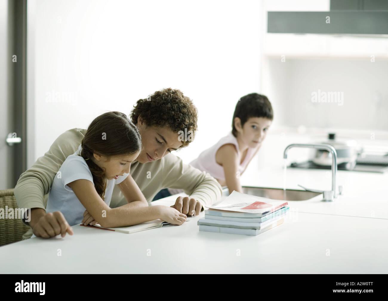 Aider un adolescent plus jeune soeur aux devoirs Photo Stock