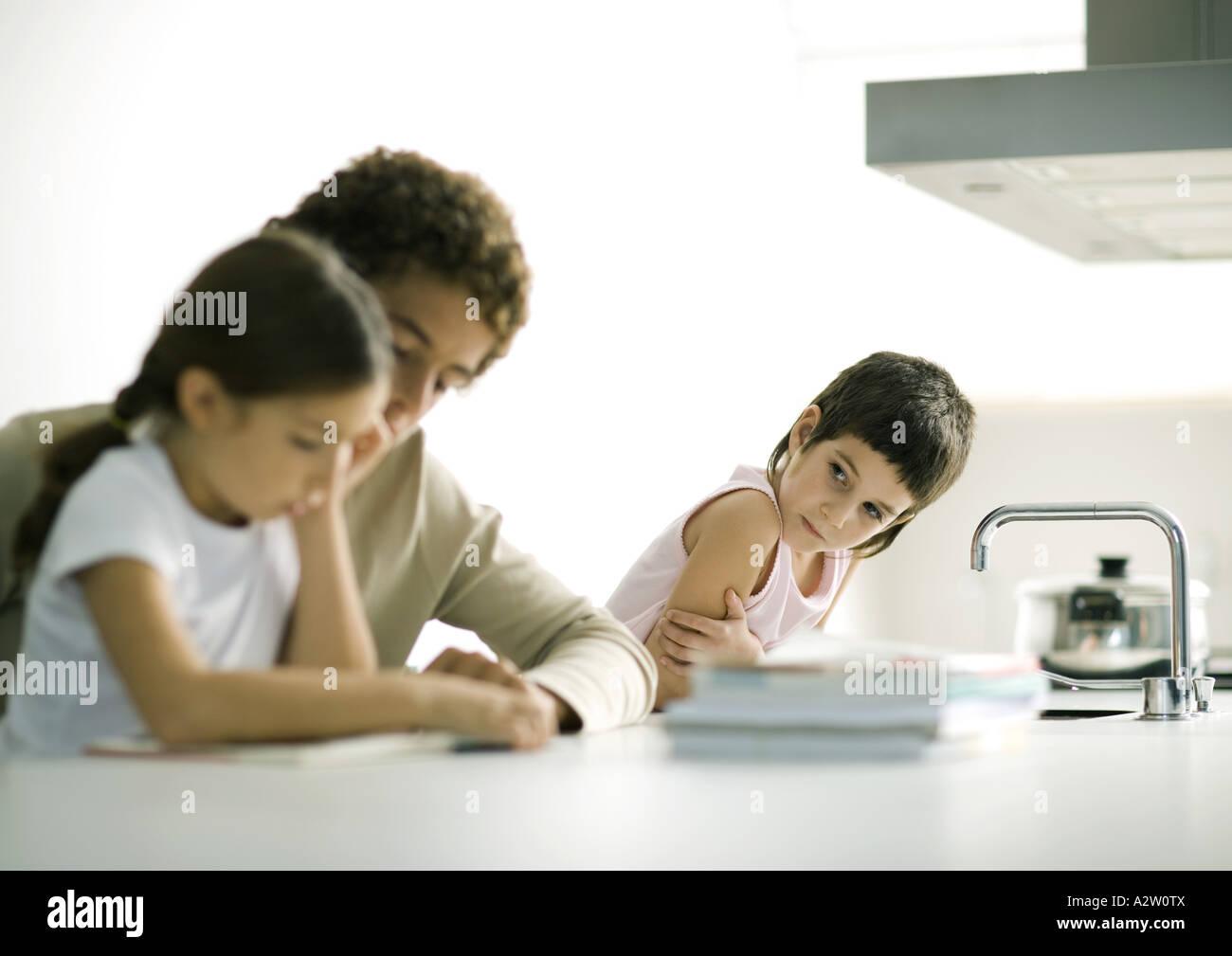 Teenage boy aider les jeunes à faire leurs devoirs, sœur deuxième sœur regarder Photo Stock