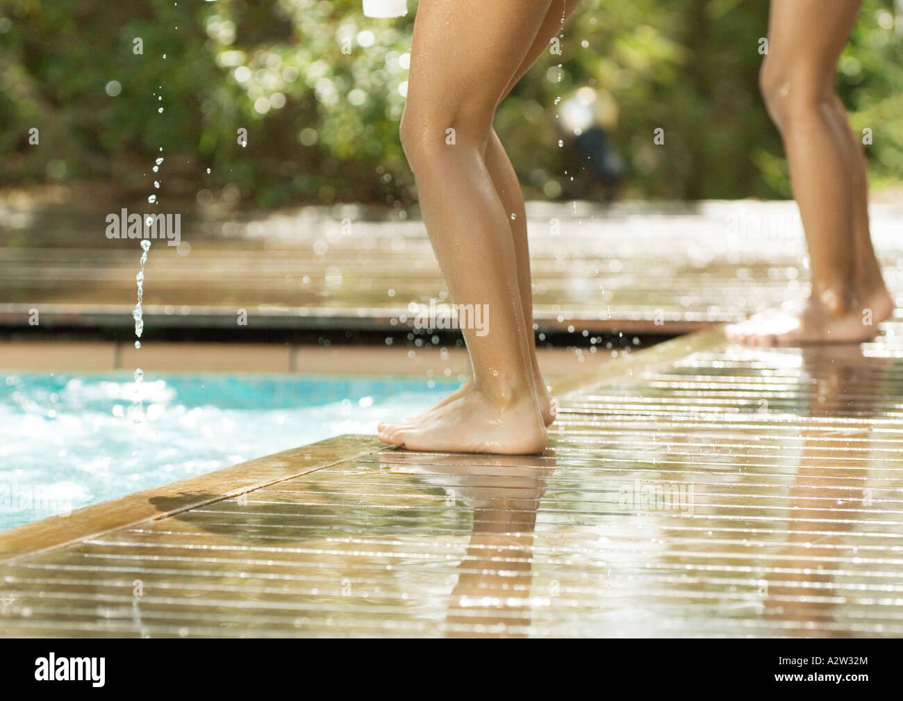 Enfants se tenant par bord de piscine, vue de la partie inférieure Photo Stock