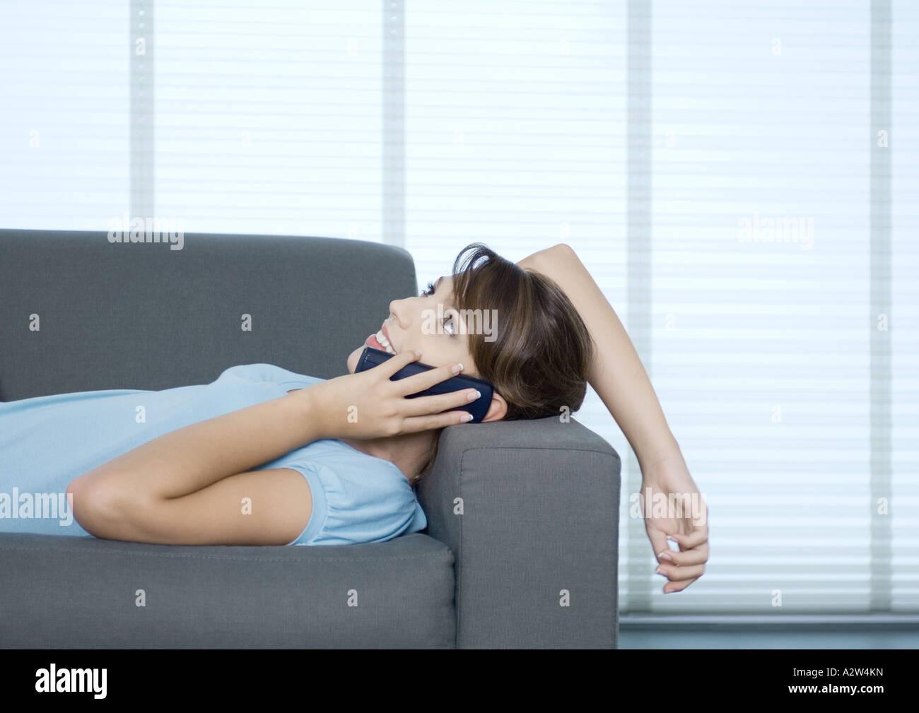 Femme allongée sur un canapé, parlant au téléphone Photo Stock