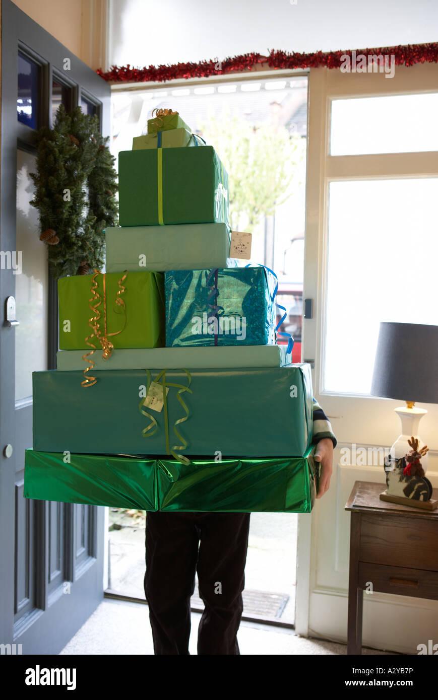 Un garçon tenant une pile de livre vert présente à travers une porte avant dans la forme d'un Photo Stock