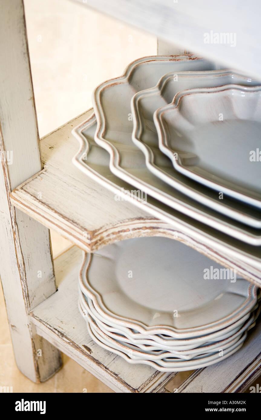 Pile d'assiettes et bols sur rayonnages peints usés Photo Stock