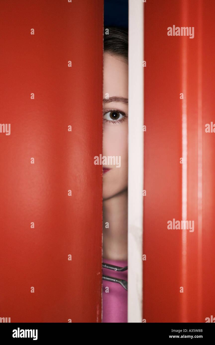 Femme derrière la porte sécurisée à la recherche de vacances Photo Stock