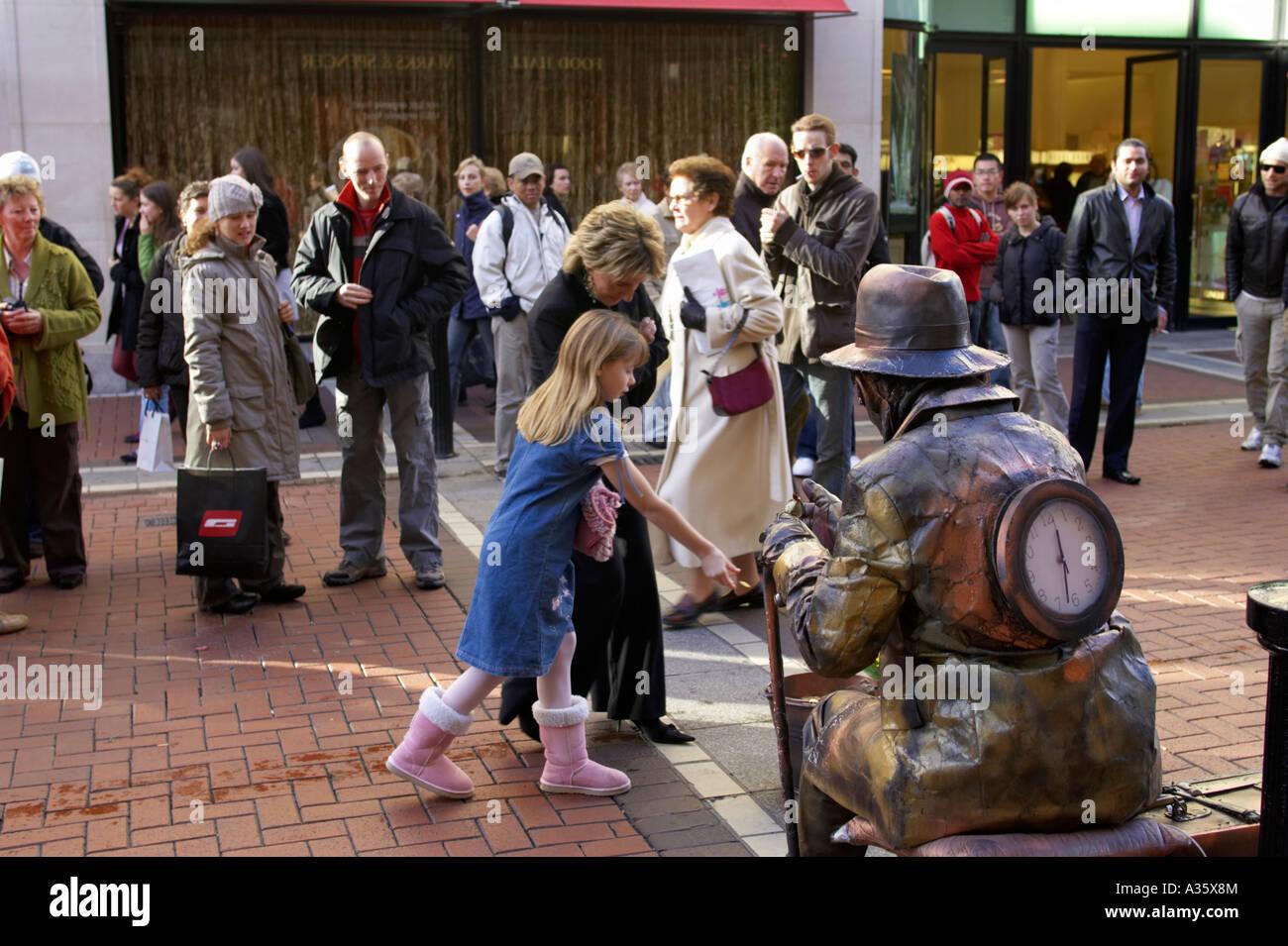 Les touristes se tenir autour de femme et de la jeune fille donnent de l'argent à street performer vêtue comme une statue de métal Banque D'Images