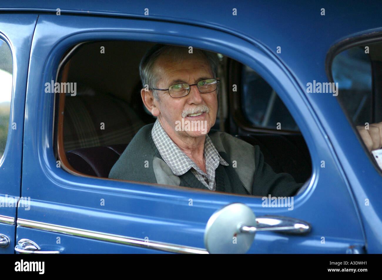 Homme d'âge moyen (60) assis en bleu 1939 6 cylindres Berline Dodge, Close up, Paeroa, Nouvelle-Zélande Photo Stock