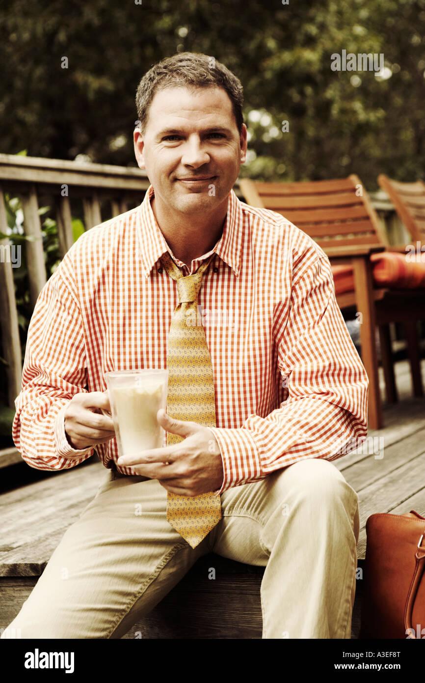 Portrait of a businessman holding a mug de milkshake et smiling Banque D'Images