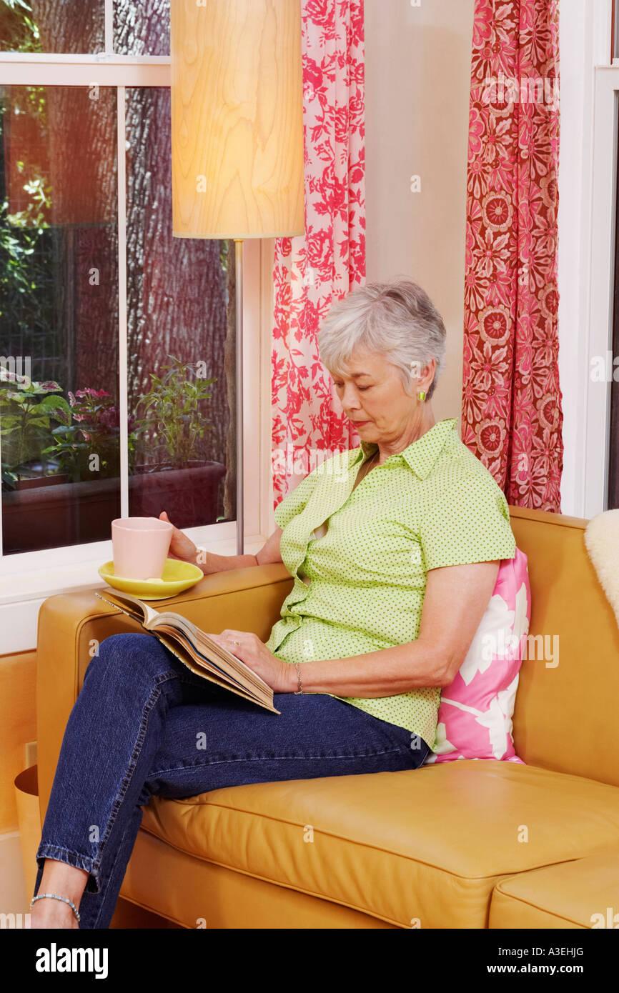 Senior woman sitting on a couch et la lecture d'un livre Banque D'Images