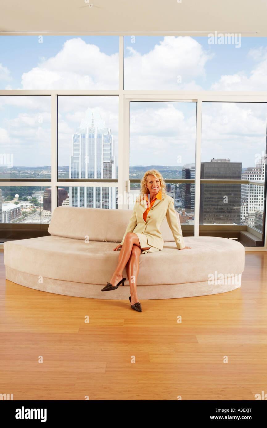 Portrait d'une femme assise sur un sofa dans un bureau Banque D'Images