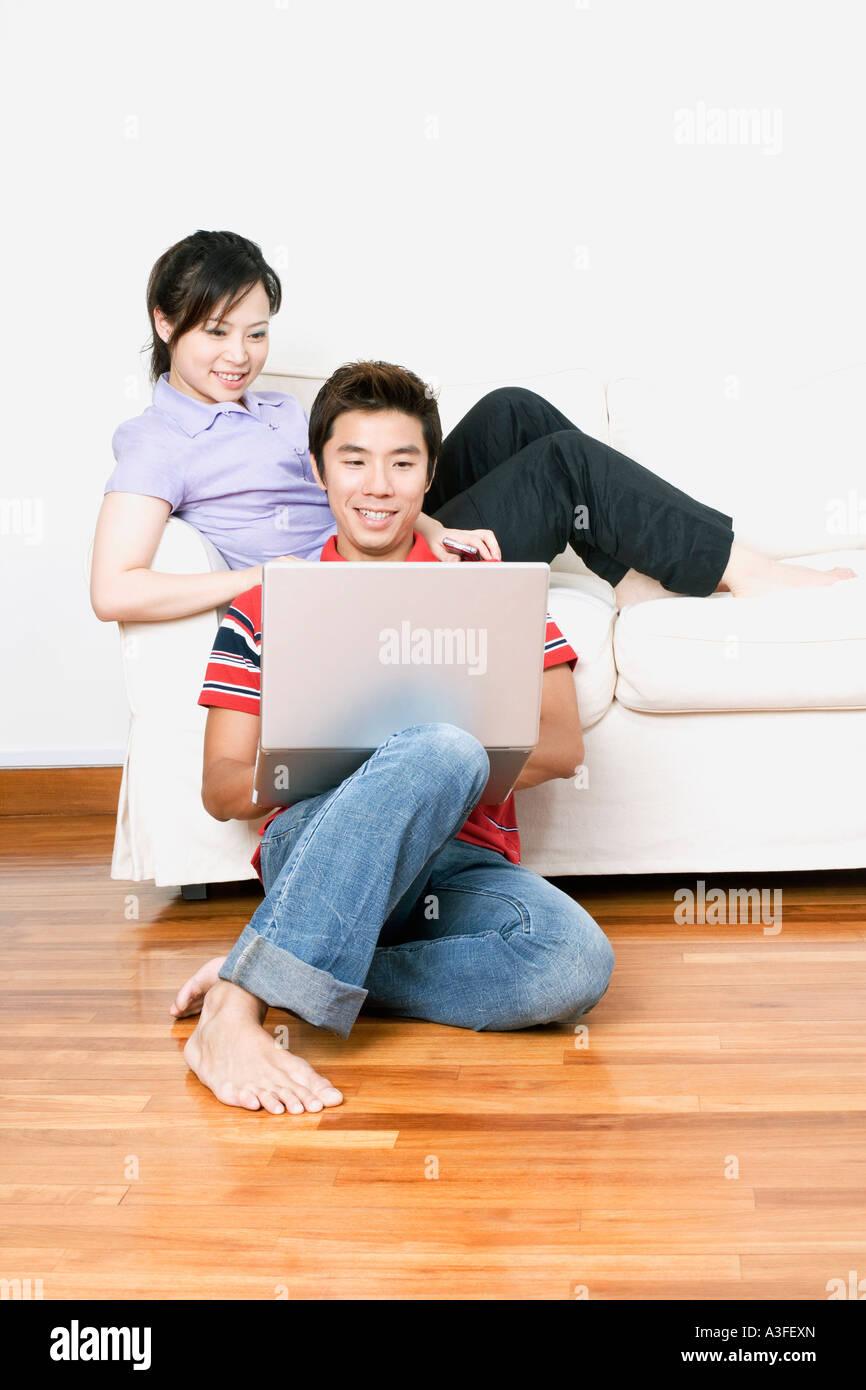 Jeune femme assise sur un canapé avec un mid adult woman using a laptop Banque D'Images