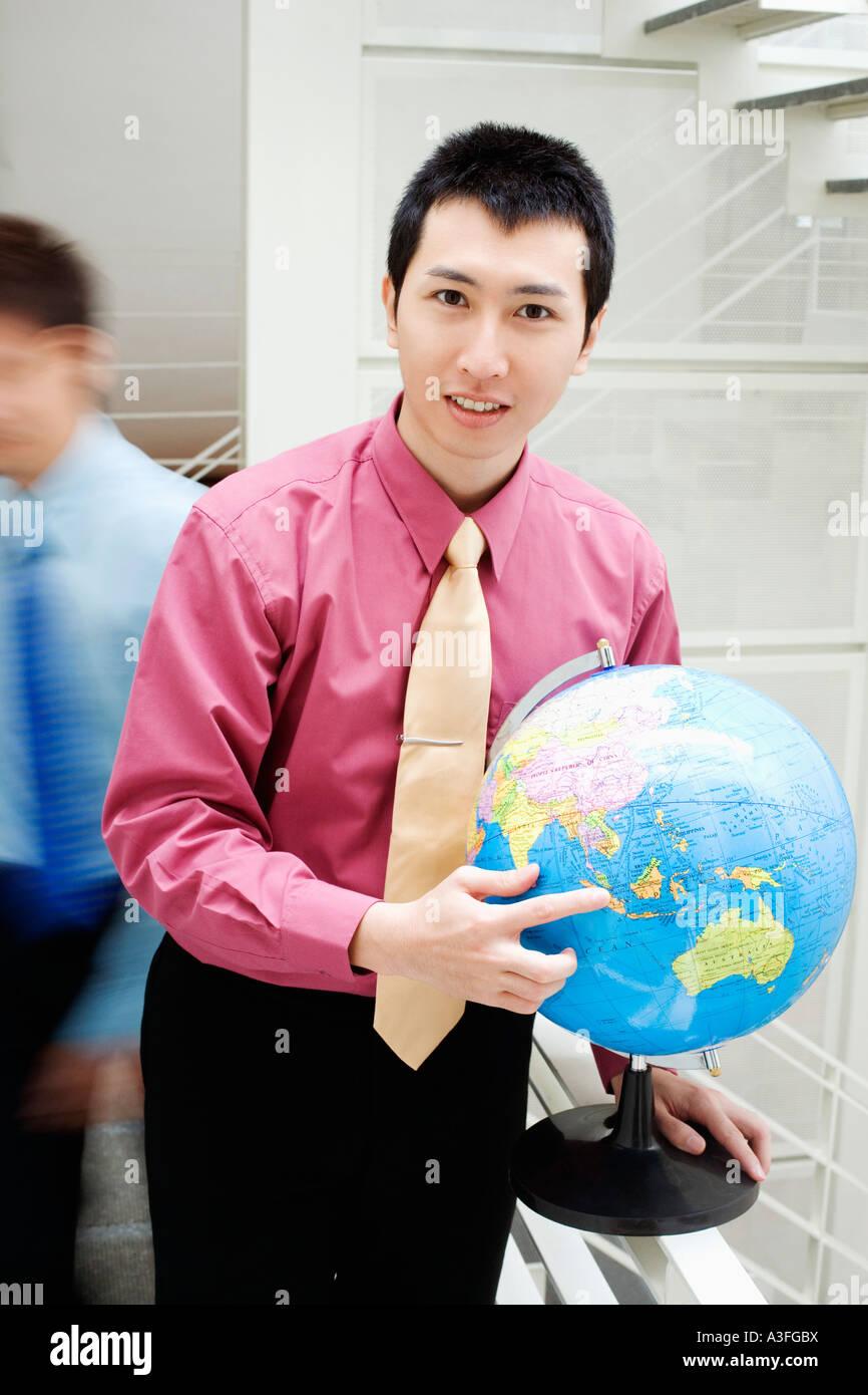 Portrait of a businessman holding a globe Banque D'Images