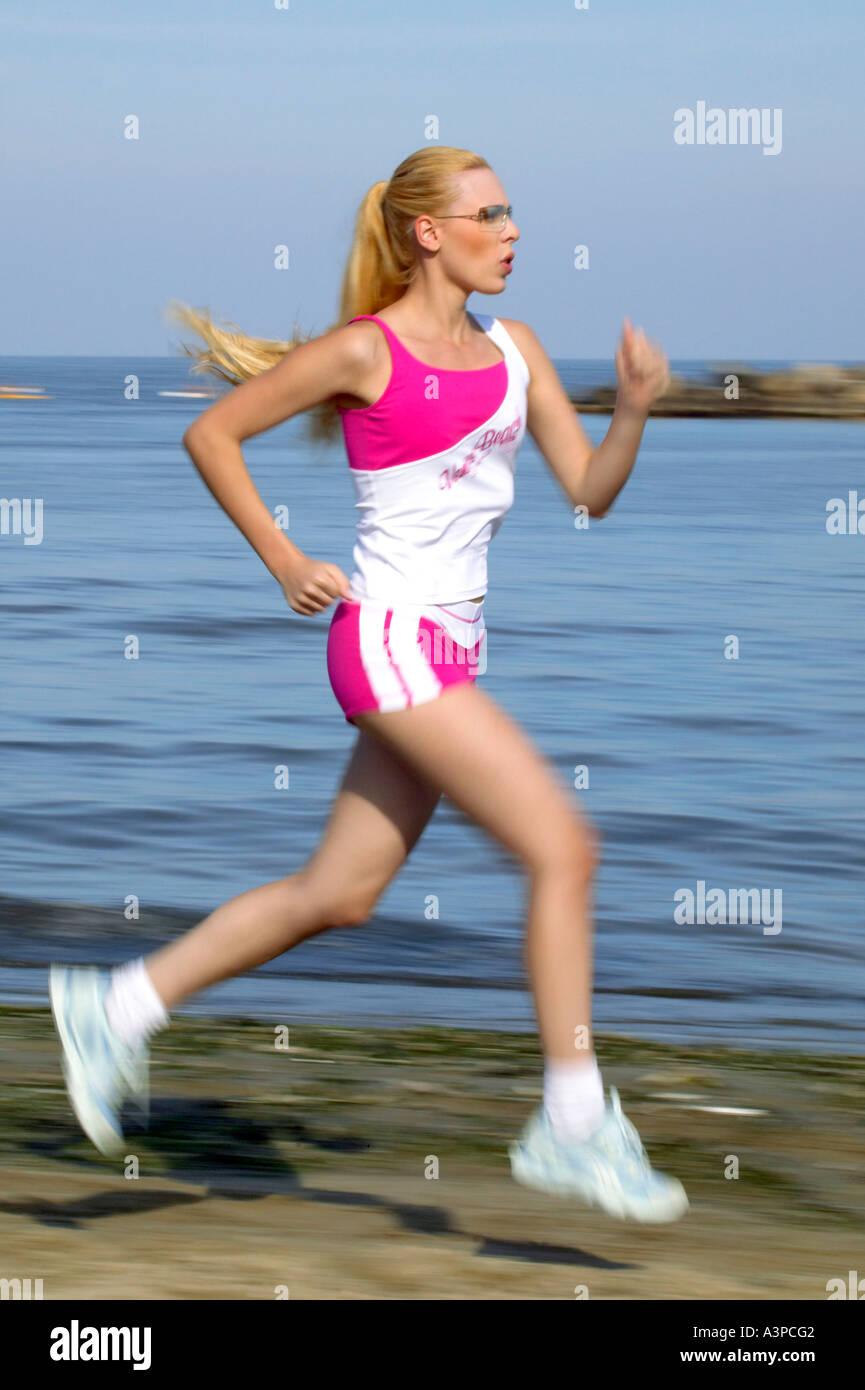 Woman jogging sur la plage Photo Stock