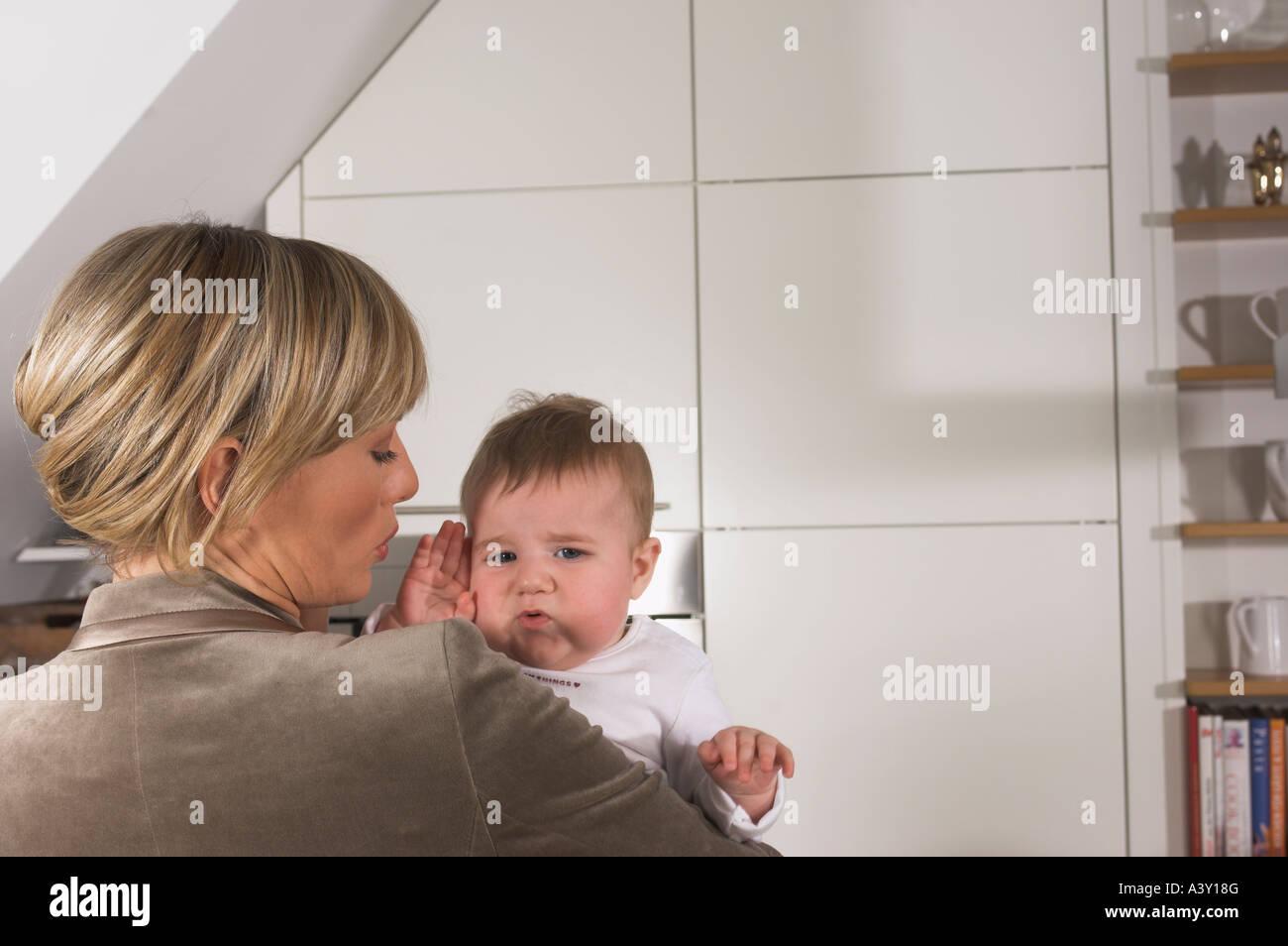 Vue arrière du souligné young businesswoman holding baby Banque D'Images