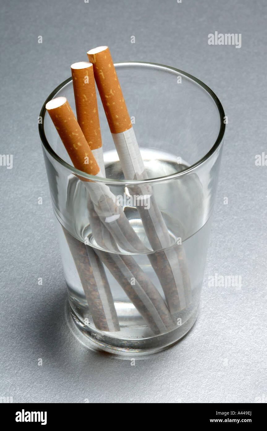 Des cigarettes dans un verre d'eau Photo Stock