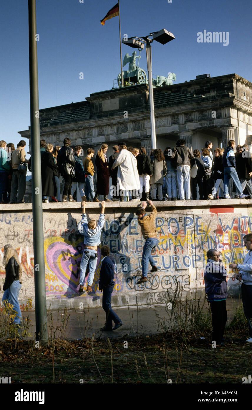 Chute du Mur de Berlin: les gens de l'Est et l'ouest de l'escalade sur le mur de Berlin à Photo Stock