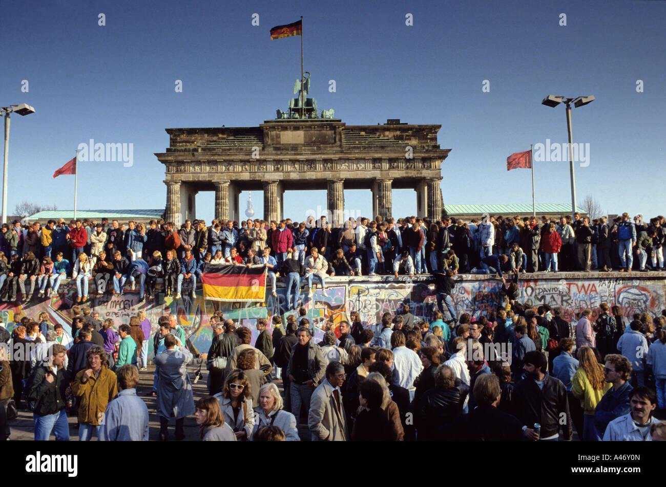 Chute du Mur de Berlin: les gens de l'Est et l'ouest de l'escalade sur le mur de Berlin à la porte de Brandebourg, Banque D'Images