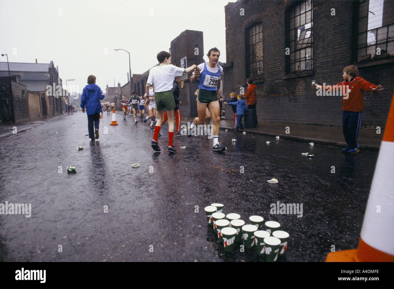 Les enfants de donner des verres d'eau aux coureurs pendant le marathon de Londres Photo Stock