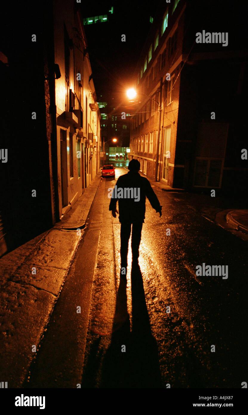La forme sombre d'un homme solitaire dans une rue de ville de nuit. Photo Stock